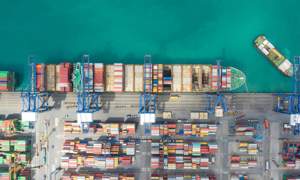 Aerial top view container cargo ship working. Business import export logistic and transportation of International by ship in the open sea.